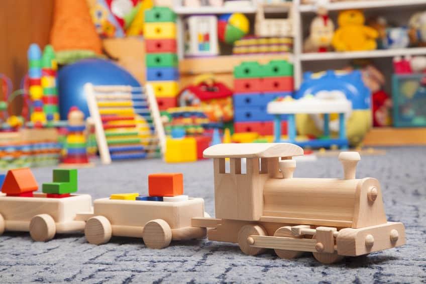 Imagem de trem de madeira e outros brinquedos ao fundo.