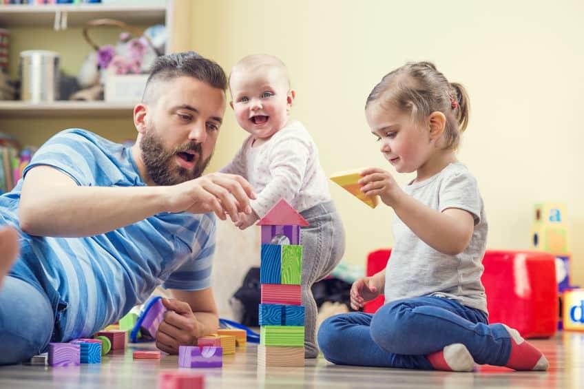 Pai e filhas brincando.