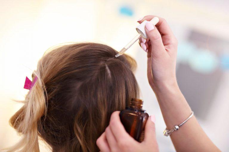 Estilista aplicando aceite sobre cabello de cliente
