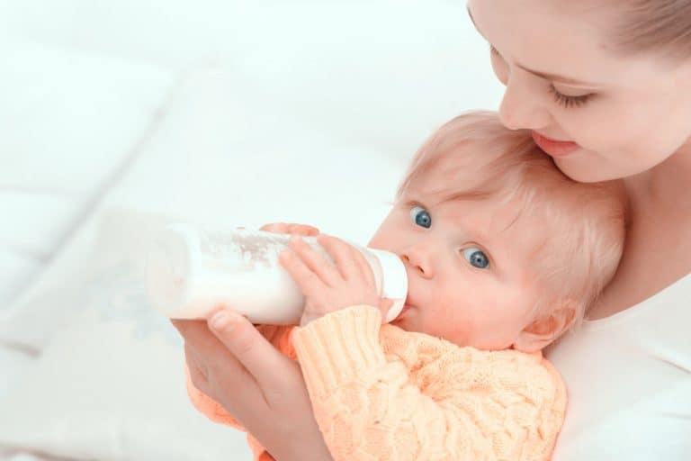 Bebê mamando com mamadeira.