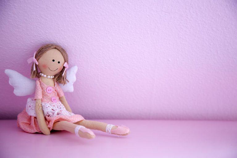 Boneca de pano sentada com asas em fundo rosa.