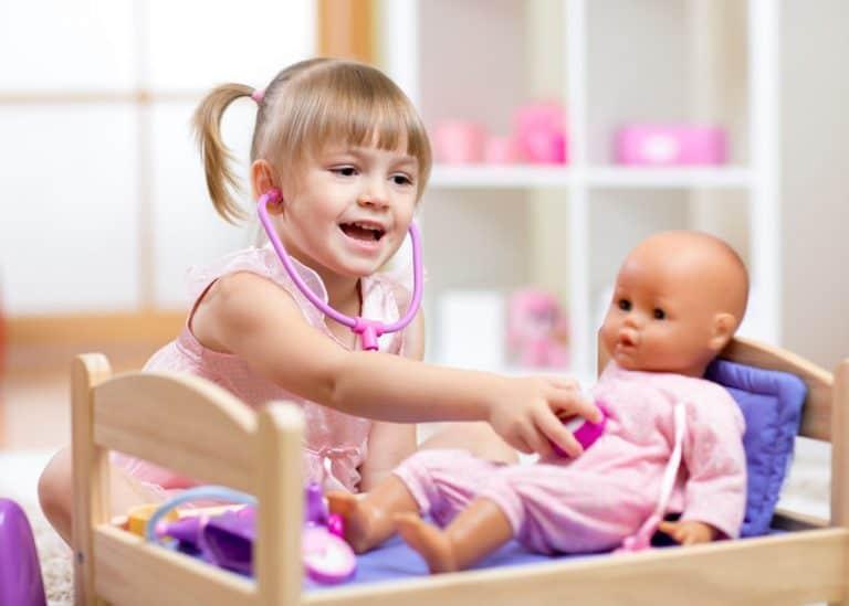 Menina brincando de médica com boneca.