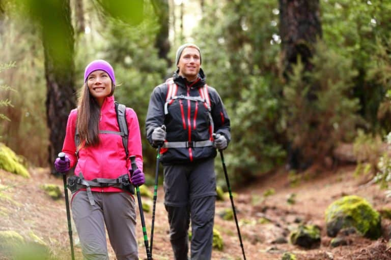 Imagem de casal fazendo trekking na natureza.