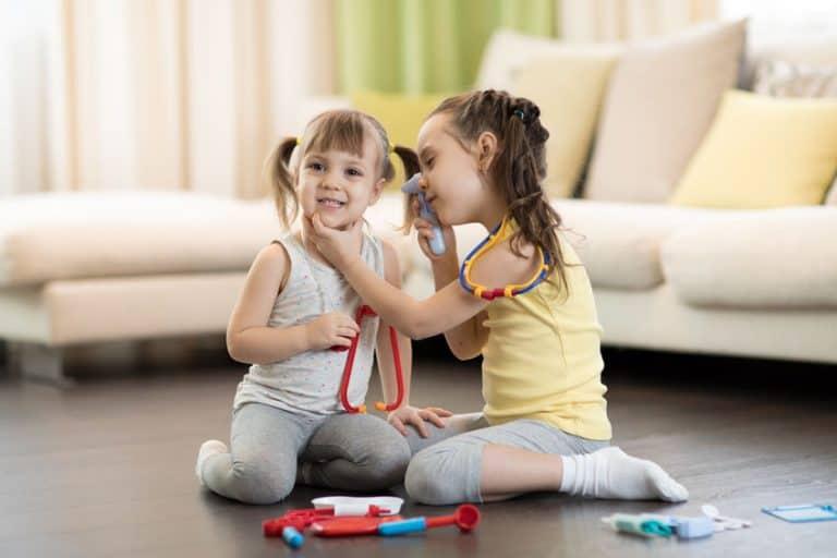 Duas meninas brincando com brinquedos de médico.
