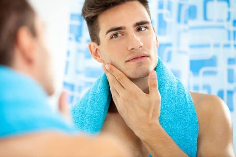 Homem em frente ao espelho passando pós-barba no rosto com toalha azul ao redor do pescoço.