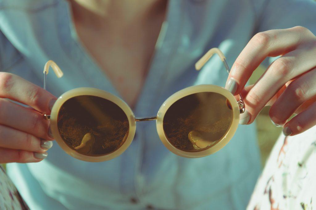 menina segurando óculos de sol amarelos