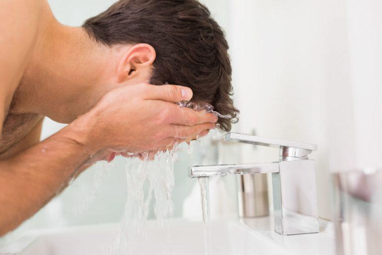 Homem lavando rosto.