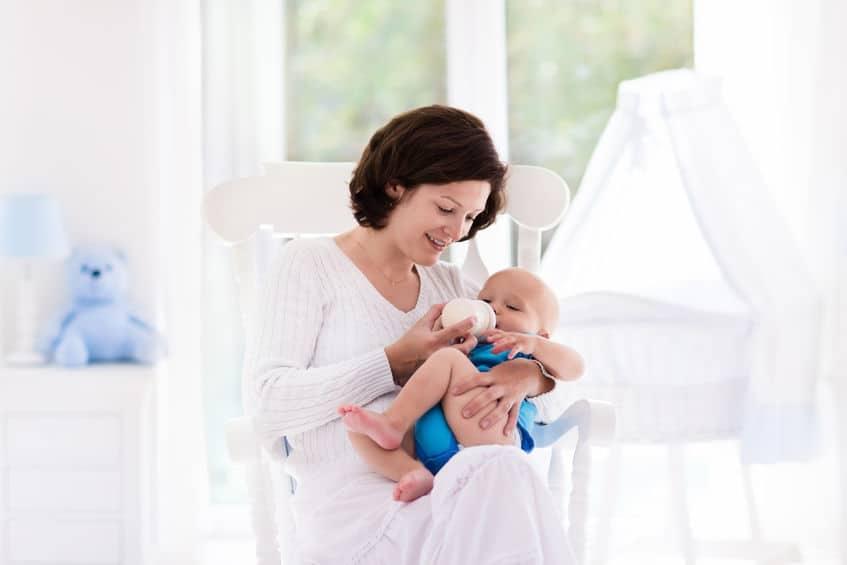 Uma mãe dando mamadeira para bebê.
