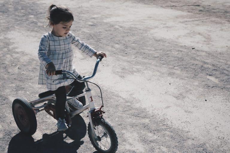 Menina andando com triciclo.