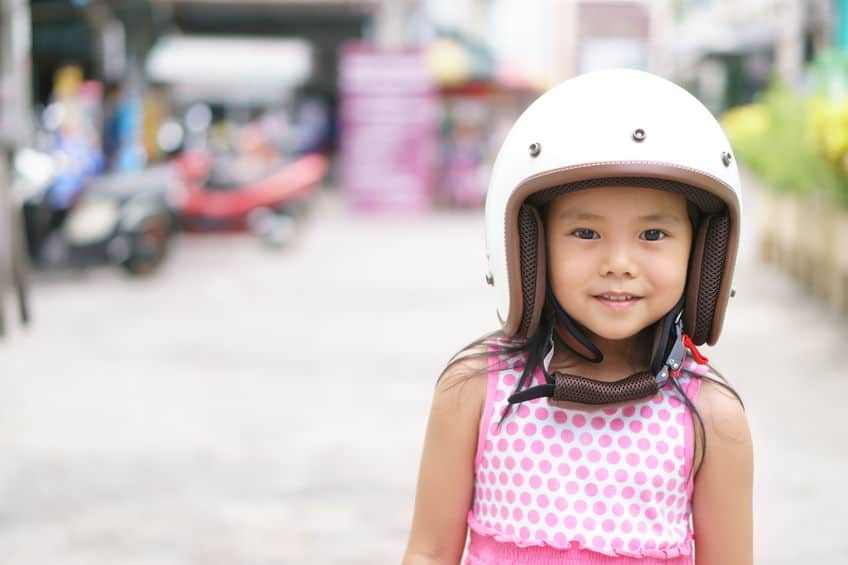 Menina com capacete branco.