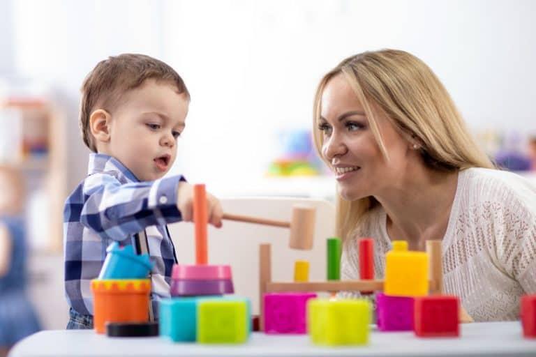 Menino brincando com brinquedo montessori.