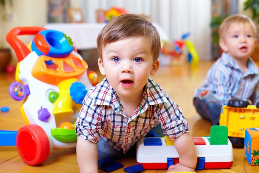 Meninos no chão com brinquedos em volta.
