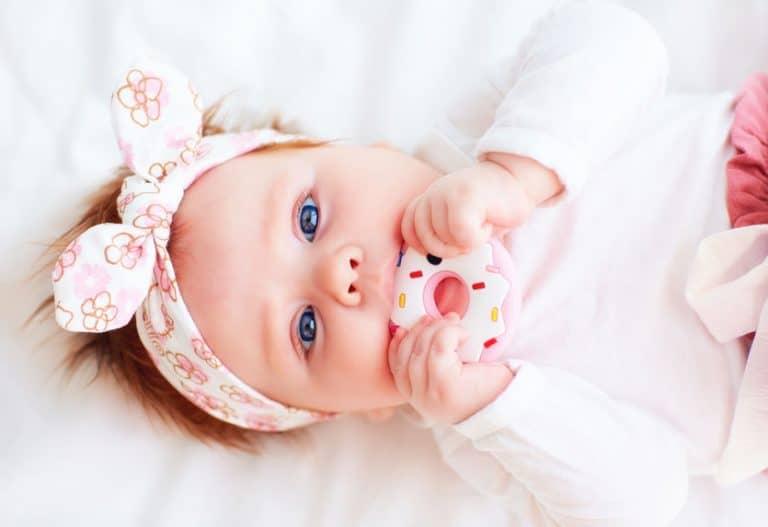 Bebê com mordedor em formato de donut.