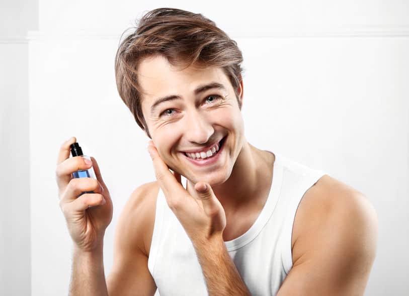 Homem passando produto no rosto.
