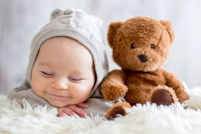 Imagem de bebê dormindo ao lado de ursinho de pelúcia.