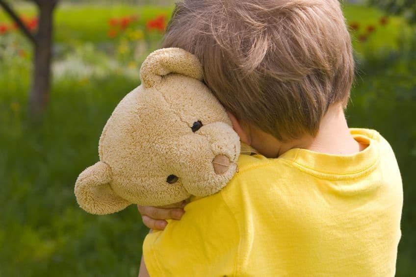 Menino abraçando urso de pelúcia.
