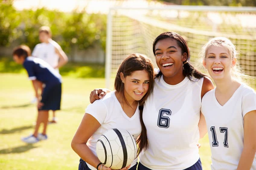 Mulheres sorrindo em jogo de futebol.