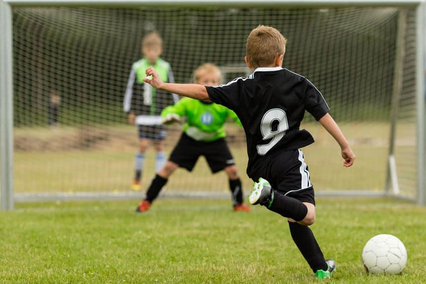Meninos jogando futebol.